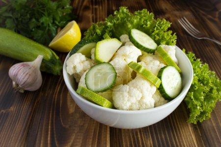Photo pour Salade végétarienne aux légumes de la plaque blanche sur le fond en bois brun - image libre de droit