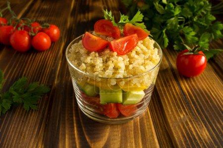 Photo pour Salade végétarienne aux légumes et au quinoa sur le fond en bois brun - image libre de droit