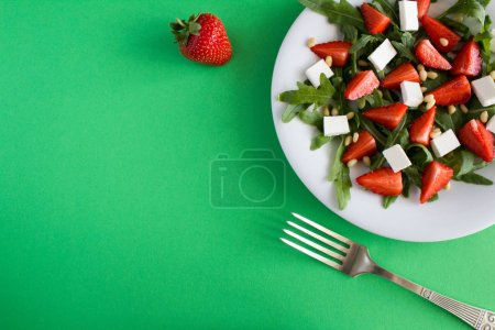 Photo pour Salade de vegatarian à la fraise, roquette, fromage mou et noix de pin dans la plaque blanche sur le fond vert. Vue de dessus. - image libre de droit