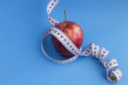 Photo pour Pomme rouge et centimètre blanc sur fond bleu. Espace de reproduction. Aliments sains. - image libre de droit