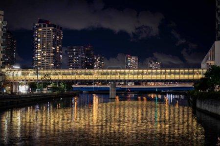 Vista del fotomontaje que conecta el edificio a través del canal en Yokohama durante la noche.