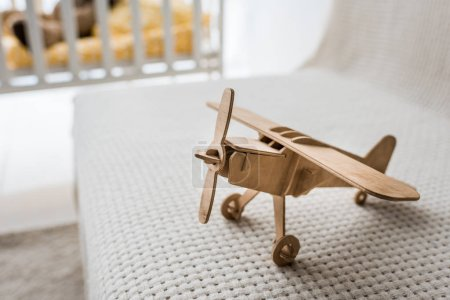 retro wooden toy plane on sofa in nursery room