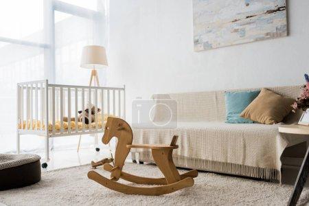 Photo pour Design intérieur moderne de salle de la pépinière avec chaise bébé et cheval à bascule - image libre de droit