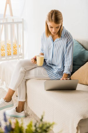 Photo for Smiling adult woman holding cup of tea and using laptop - Royalty Free Image