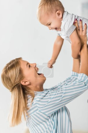Photo for Cheerful mother looking at toddler and holding him in hands on white background - Royalty Free Image