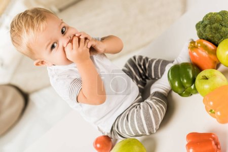 Photo for Cute toddler eating and sitting on table surrounded by fruit and vegetables - Royalty Free Image