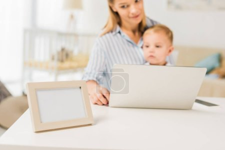 Photo for Mother sitting at desk with cute toddler while using laptop, focus on foreground - Royalty Free Image