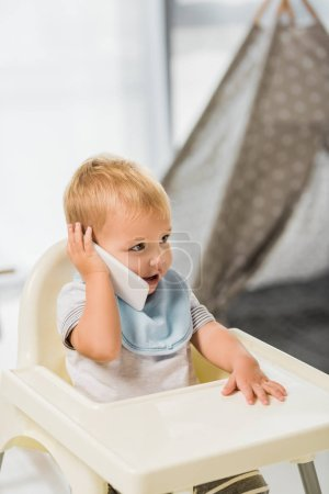 cute toddler talking on smartphone and sitting in baby chair