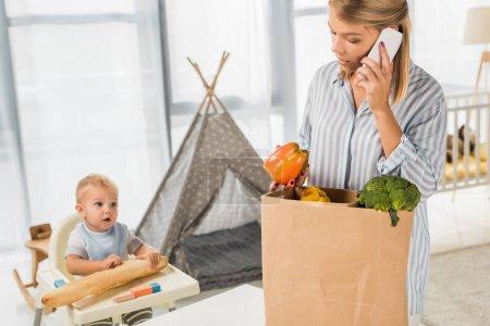 Photo pour Occupé mère tenant épicerie tout en parlant sur smartphone avec tout-petit dans la chaise de bébé sur fond - image libre de droit