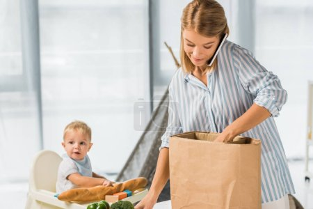 Photo for Mother holding groceries while talking on smartphone with toddler in baby chair on background - Royalty Free Image