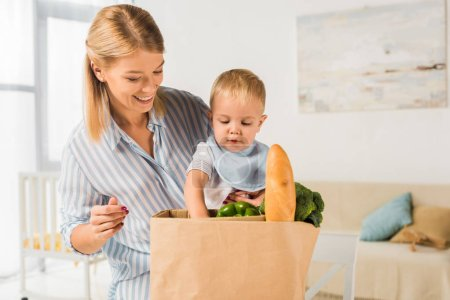 cheerful happy mother showing groceries to son
