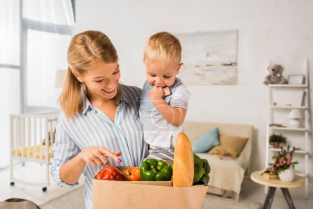 smiling happy mother showing groceries to son