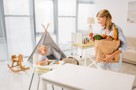 mother carrying groceries and looking at son in baby chair