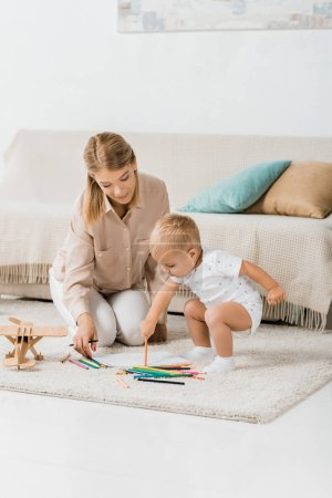 Photo for Happy mother and adorable toddler drawing together in nursery room - Royalty Free Image