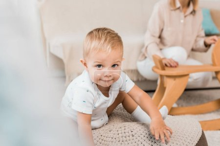 adorable toddler sitting and looking at camera with mother on background