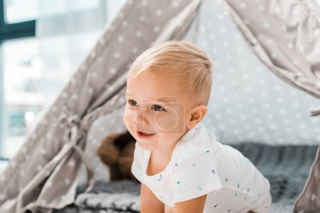 Photo for Smiling adorable toddler with baby wigwam on background - Royalty Free Image