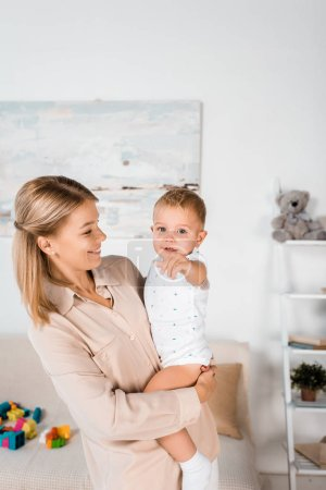 smiling mother holding adorable toddler pointing at camera