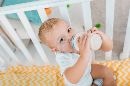 Photo for Adorable toddler drinking out of baby bottle in crib - Royalty Free Image