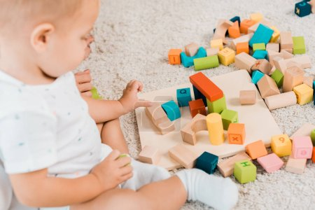 Photo for Side view on adorable toddler playing with colorful cubes - Royalty Free Image