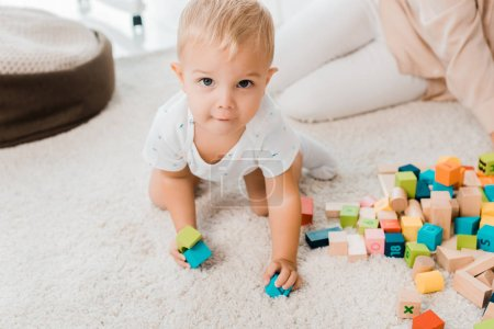 adorable toddler playing with colorful cubes and looking at camera
