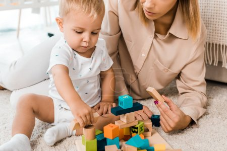 cropped view of adorable toddler playing with colorful cubes and mother in nursery room