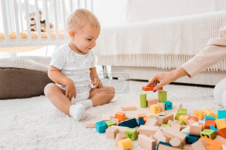 adorable toddler playing with colorful cubes in nursery room