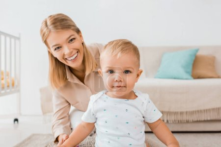 adorable toddler looking at camera with mother in nursery room