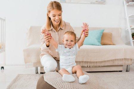 Photo pour Adorable bambin, levant les mains vers le haut avec la mère dans la salle de la pépinière - image libre de droit
