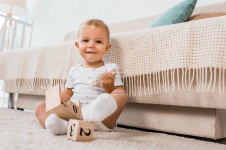Photo for Adorable toddler with play cubes sitting and looking at camera - Royalty Free Image