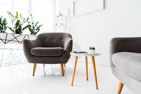 Photo pour Intérieur moderne de salle d'attente blanche avec fauteuils gris et table - image libre de droit