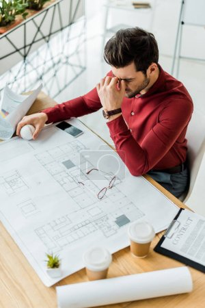 Foto de Stressed male architect having headache while working on blueprint in office - Imagen libre de derechos