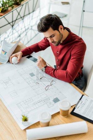 Photo pour Beau architecte masculin assis et travail sur plan directeur au bureau - image libre de droit
