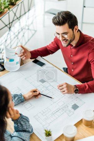 Foto de Pareja de arquitectos sentados en mesa y trabajando en planos en oficina - Imagen libre de derechos