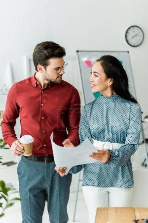 Photo pour Smiling couple multiculturel des architectes travaillant sur plan directeur au bureau - image libre de droit