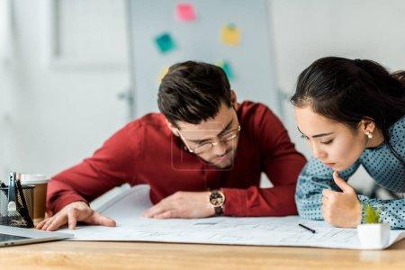 Photo pour Concentré de couple multiculturel des architectes travaillant sur plan directeur au bureau - image libre de droit