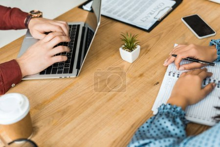 Photo for Partial view of colleagues sitting at table and using laptop in office - Royalty Free Image