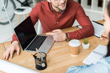 Photo pour Vue recadrée de collègues assis à table et à l'aide d'ordinateur portable avec écran blanc au bureau - image libre de droit
