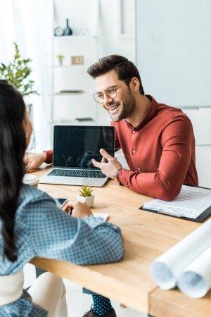 Foto de Arquitecto hombre sentado en la mesa y señalando con el dedo en el portátil con pantalla en blanco en la oficina - Imagen libre de derechos