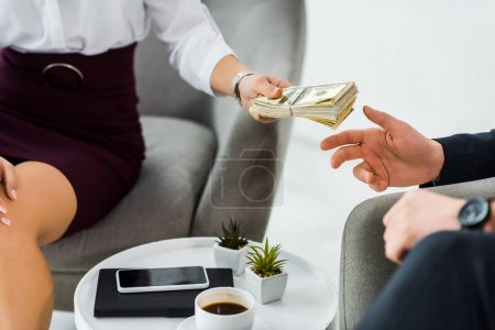 Photo for Cropped view of businesswoman giving money to businessman in office - Royalty Free Image