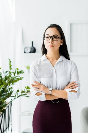Photo pour Beautiful confident asian businesswoman in formal wear and glasses with arms crossed in office - image libre de droit