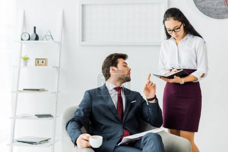 Photo for Asian businesswoman writing in notebook while businessman sitting and having coffee break in office - Royalty Free Image