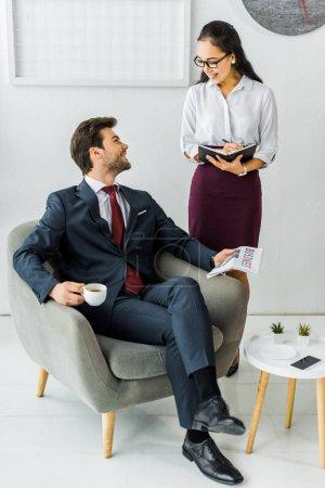 Photo pour Femme d'affaires asiatique, écrire dans cahier tandis que l'homme d'affaires, assis sur le fauteuil avec le journal et le café au bureau - image libre de droit