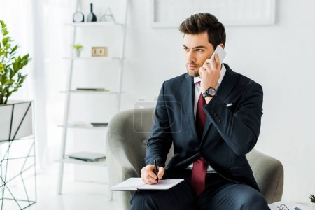 handsome businessman in formal wear sitting on armchair and witting in notebook while talking on smartphone in office