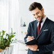 handsome smiling businessman in formal wear writing in notebook in office
