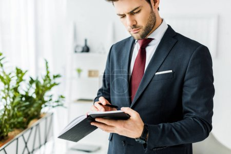 Photo for Handsome businessman in formal wear writing in notebook in office - Royalty Free Image