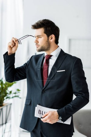 handsome businessman in formal wear holding newspaper and putting on glasses in office