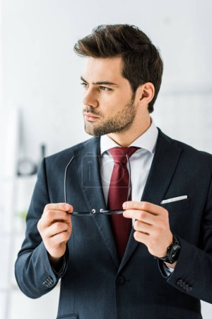 handsome businessman in formal wear putting on glasses in office