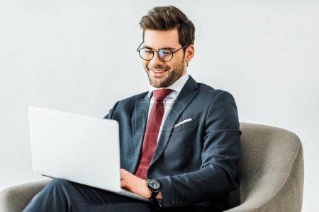 Photo pour Homme d'affaires souriant en tenue formelle assis sur un fauteuil et utilisant un ordinateur portable au bureau - image libre de droit