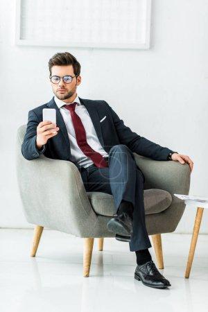 schöner Geschäftsmann in formeller Kleidung, der auf einem Sessel sitzt und sein Smartphone im Büro benutzt