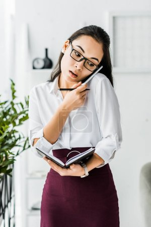 asian businesswoman talking on smartphone while holding notebook in office
